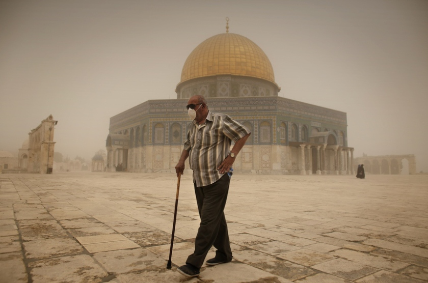 A Palestinian man wears a mask to protect his face from the dust as he walks past the Dome of the Rock mosque in the al-Aqsa Mosque compound, during a sandstorm on September 8, 2015, in the old city of Jerusalem. A massive sandstorm has blanketed much of the Middle East. Large parts of Lebanon, Israel and Cyprus were shrounded in a thick cloud of dust that meteorologists said had swept in from Iraq and Syria.  AFP PHOTO / AHMAD GHARABLI         (Photo credit should read AHMAD GHARABLI/AFP/Getty Images)